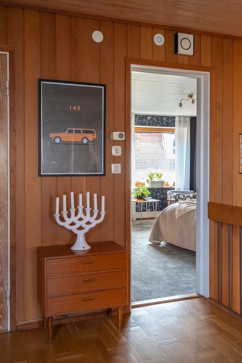 Teakbyrån utanför parets sovrum är fyndad på en loppmarknad. Ljusstaken som ursprungligen kommer från Guldkroken i Hjo är även den ett loppisfynd.
