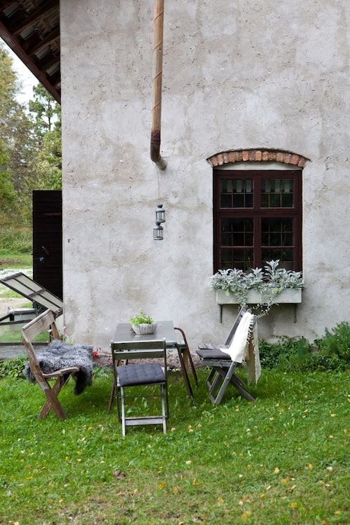 Vid ena kortsidan står en utegrupp som Marie arrangerat av en gammal kyrkbänk, några loppisköpta trästolar och en bockad metallskiva, som vilar på ihopsatta armeringspinnar.