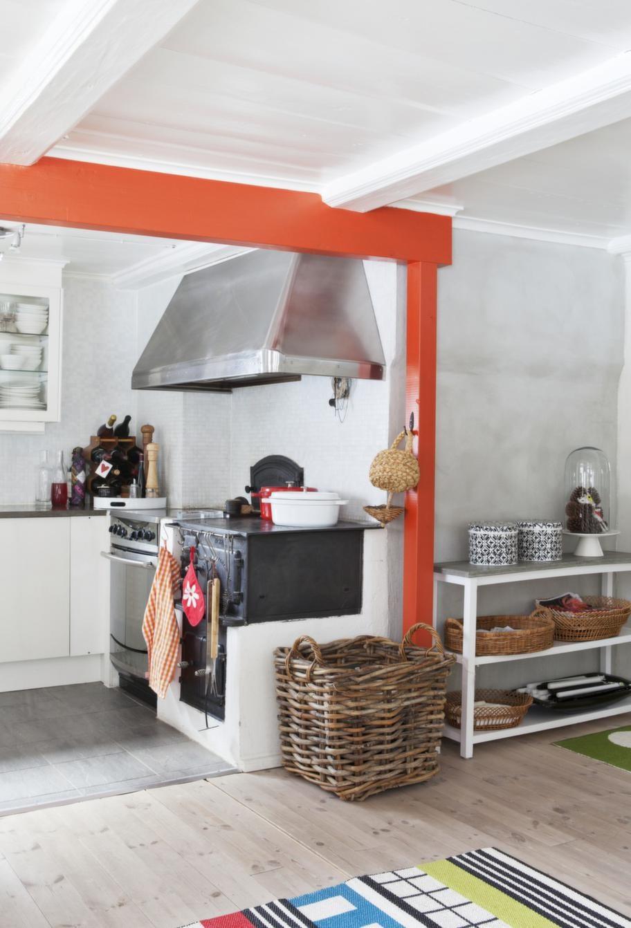 Bjälkarna i taket är målade i en stark orangeröd färg och det ger köket karaktär. Kåpan över spisen är gjord av en lokal plåtslagare.