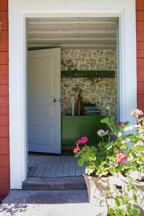 Josef Franks tapet passar fint i hallen där ett loppisfyndat skåp och en hemsnickrad krokbräda målats i matchande grönt. Tapet Vårklockor, från Svenskt Tenn.