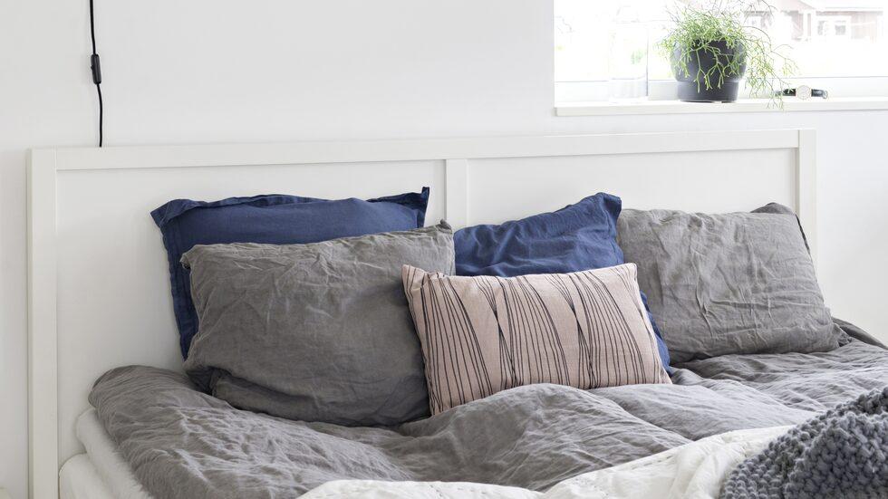 I sovrummet är väggarna vilsamt vita. Sängen kommer från Ikea, vägglampan från Granit, överkast och pläd från H&M home.