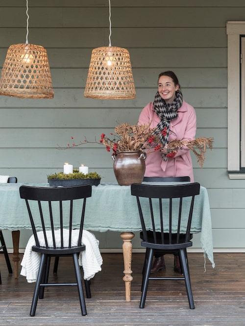På duken, som är ett enkelt linnetyg köpt som metervara, står en stor Höganäskruka med säsongens skörd från naturen. De fina lamporna är köpta på Clas Ohlson.
