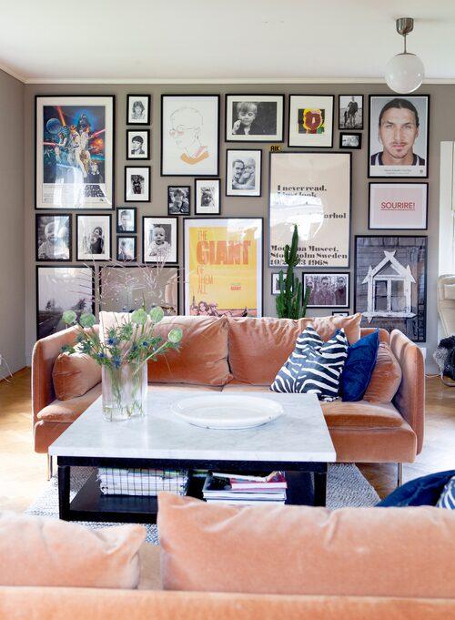 Tavelvägg i vardagsrummet. Zebrakudde från H&M home och jeanskudde från Ikea. Tavelväggen består av bland annat familjefotografier och bilder tagna av Frida själv. Zlatanporträttet av Martin Schoeller är från Fotografiska. Plansch med Andy Warhol-citat från Moderna museet.