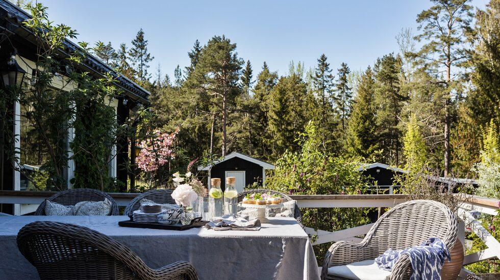 På altanen är det uppdukat för fika. Pläd och tårtfat, Miljögården. Matbord, Jysk. Linneduk och servetter, Himla. Glaskaraffer, Ikea.