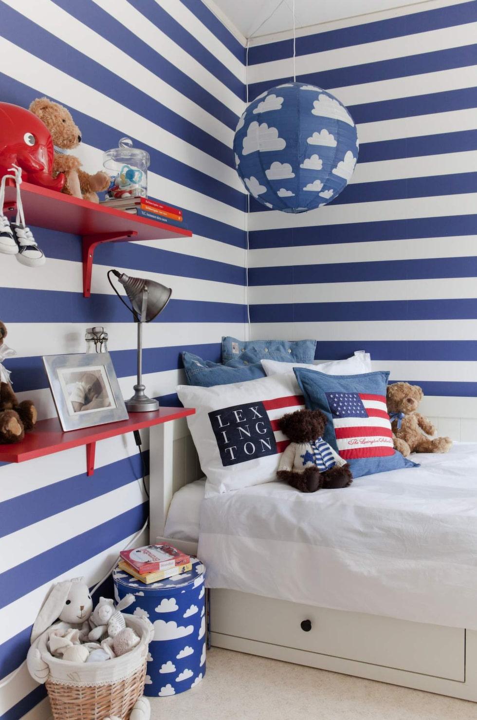 Älskade ränder. Mysig sänghörna med kuddar från Lexington, förvaringsbox och lampa med moln från Färg & form. Röda vägghyllor från Ikea.