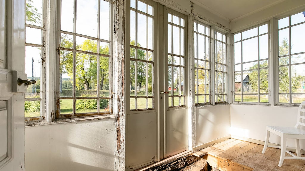 Inglasad veranda med vackra fönsterbågar och dubbeldörrar. Här hade delar av golvet tagits upp för att ta bort organiskt material i grunden.