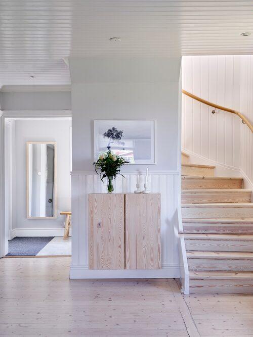 När Uffe och Sofia lät renovera golven, från plastmatta till ljust trä, så fick även trappan en make over. Spegeln har Uffe byggt. Skåpet från Ikea har fått vit bets. Ljusstakar, Iittala.