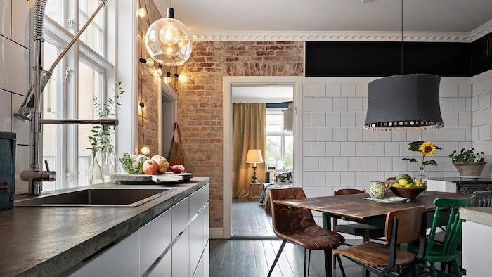 Betongbänkskiva och vedeldad köksspis samt plats för stort köksbord.
