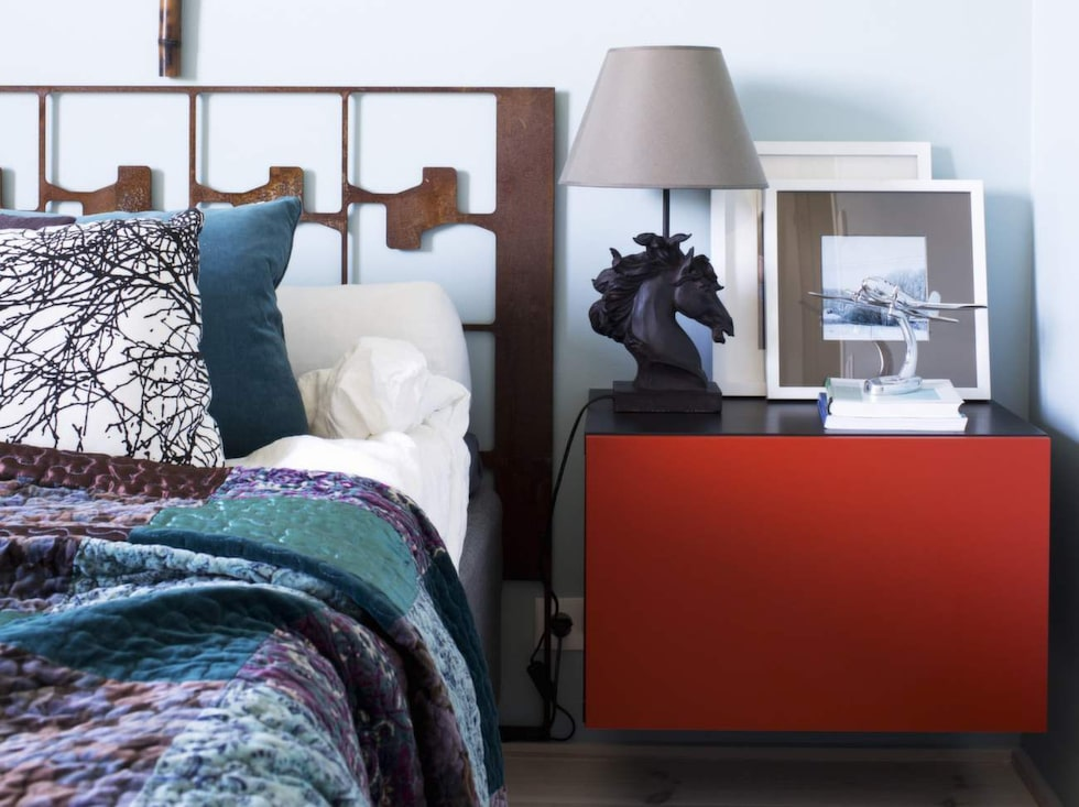 Spännande detaljer. Sänggavel i rostigt stål av okänd konstnär. Överkast från Indiska. Sängskåp från Ikea.