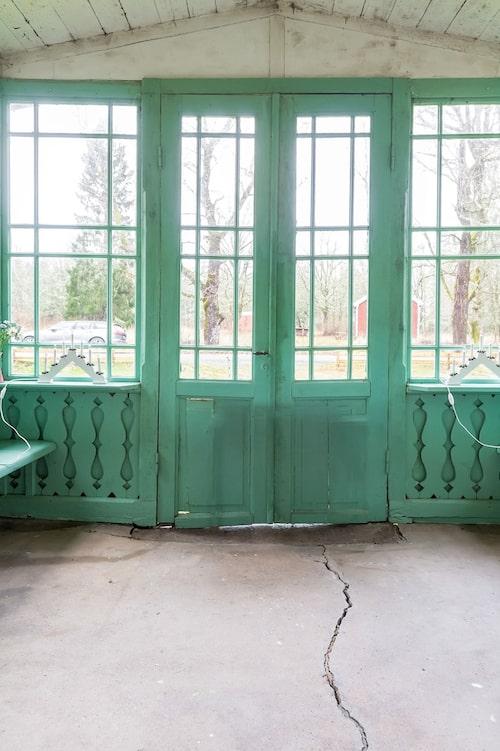 Den turkosa glasverandan med spröjsade fönster och fina snickerier sticker ut.