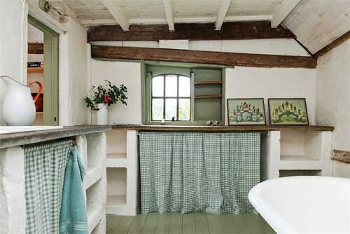 Det lantliga badrummet med stenväggar och takbjälkar.