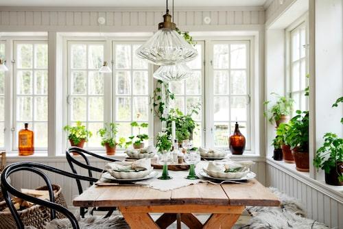 Det är dukat för vårmiddag på en ljusa inglasade verandan. Thonet-stolar, Royal Design. Bord, auktionsfynd. Lampor, Jotex. Bänk, Hjärterum Interiör.