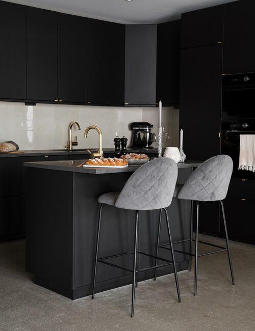 Köket är placerat mitt i huset med öppen planlösning och en praktisk köksö med inbyggd fläkt som gör att man inte behöver installera någon skrymmande takfläkt. Barstolar från Chilli.