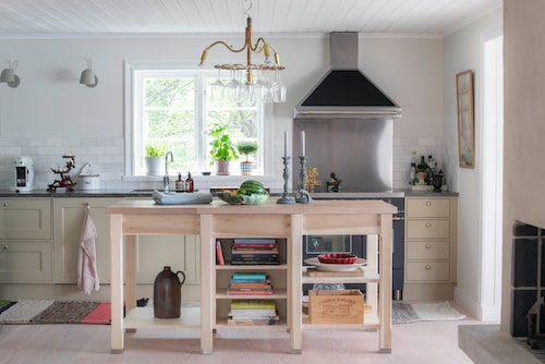 Modern design bryter av fint mot köket i gammaldags stil. Köksön är specialbyggd efter egen design. Kök, Hagaköket. Taklampa i koppar med ställning för vinglas, från Örsjö. Den färgglada mattan Gan är designad av Patricia Urquiola.