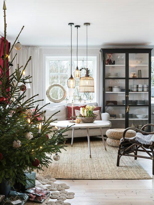I vardagsrummet skapar blommor och levande ljus julstämning tillsammans med granen. Lampor och kuddar, från Butik botanik. Soffbordet är ett omgjort Ikea-bord. Paret har bytt skiva och slipat bort färgen. Kristofer har byggt vitrinskåpet.