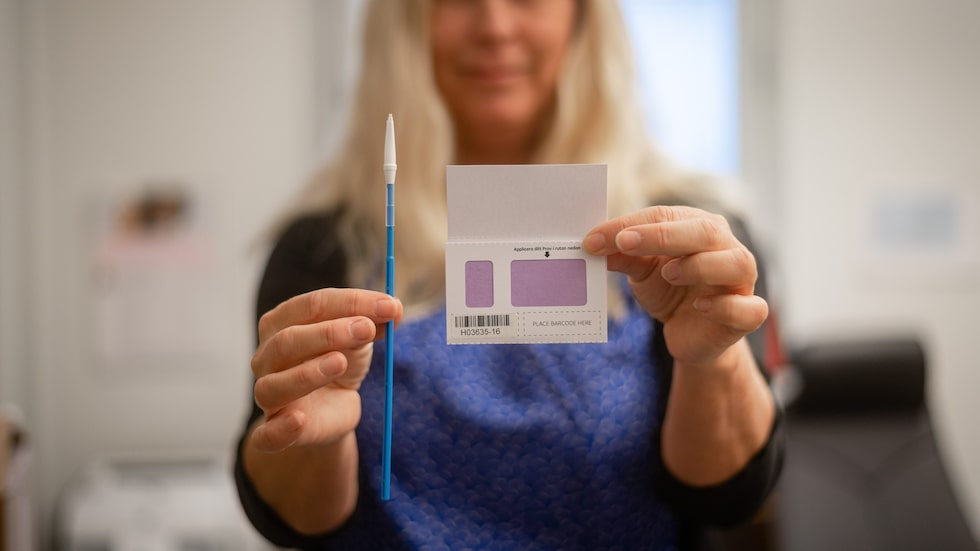 Inger Gustavsson visar upp provtagningskortet och silikonborsten som kvinnan använder för att ta sitt cellprov. Efter provtagningen rullar kvinnan borsten på kortet som direkt ger konfirmation att testet är klart i form av en färgförändring på papperet. Därefter skickas papperet in med post.