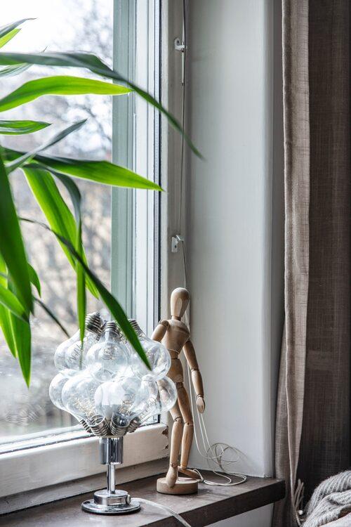 Lampan i fönstret har Malin gjort av en lampfot och lampor från en solcellsslinga som hade slutade fungera.