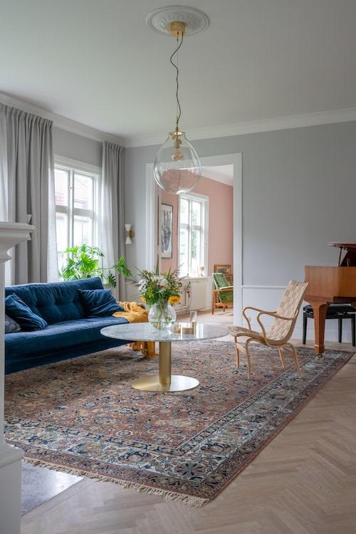 Evelina och Andreas har skapat ett personligt hem med en blandning av både nya och gamla möbler. Fåtöljen Eva i design av Bruno Mathsson och mattan fanns i huset när de tog över det. Soffa, Melimeli. Soffbord, Mio. Taklampa, Hemmahallen.