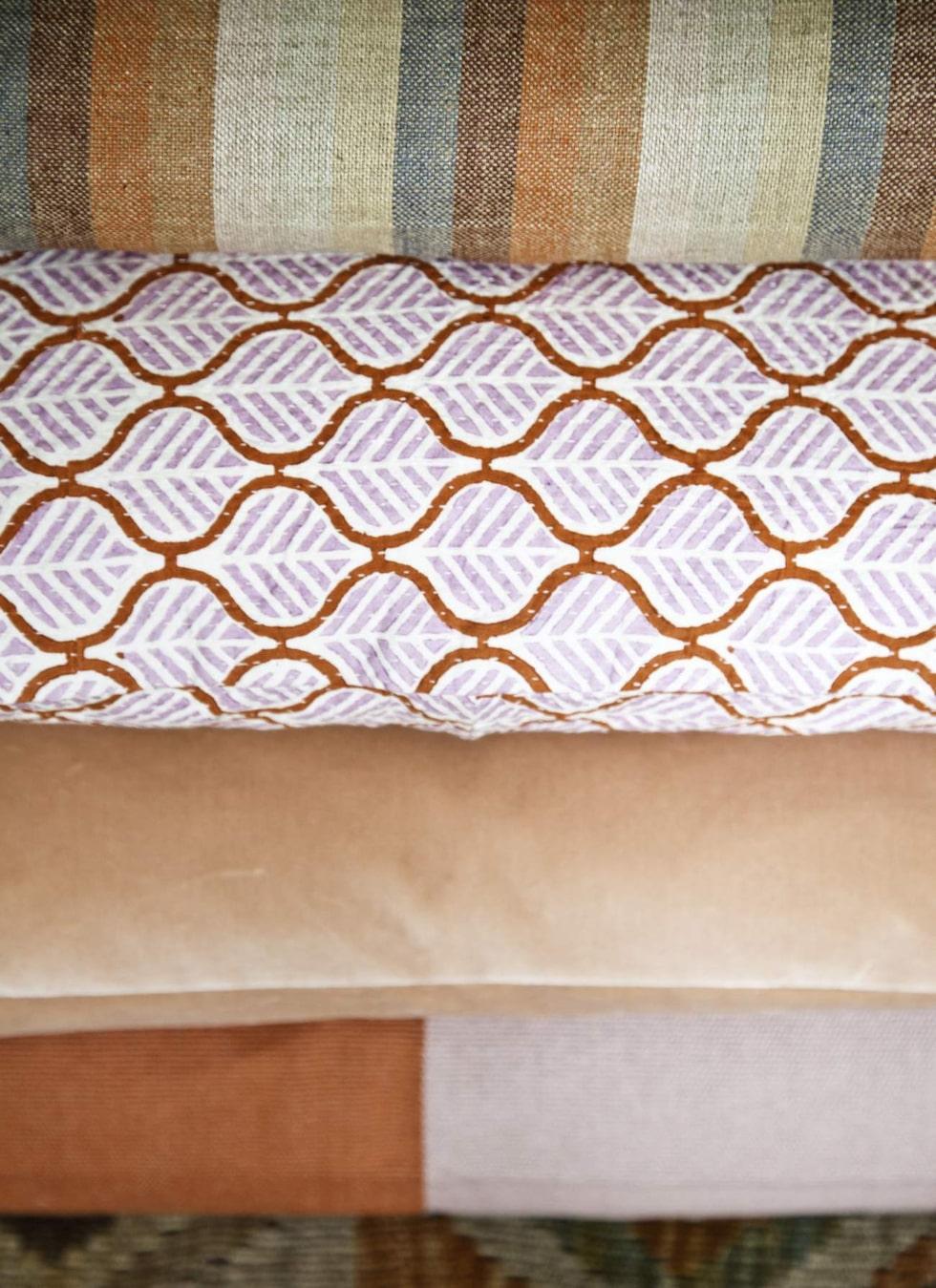 Detalj från kuddarna på golvet: Rutmönstrad kudde, 249 kronor, Afroart. Aprikosfärgad sammetskudde, 1 800 kronor, Garbo interiors. Sittkudde Bruce,  299 kronor, Linum.