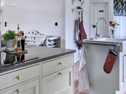 Diskmaskin och ugn är uppbyggda i arbetshöjd, vilket är bekvämt för ryggen. Kökssoffa, loppis.