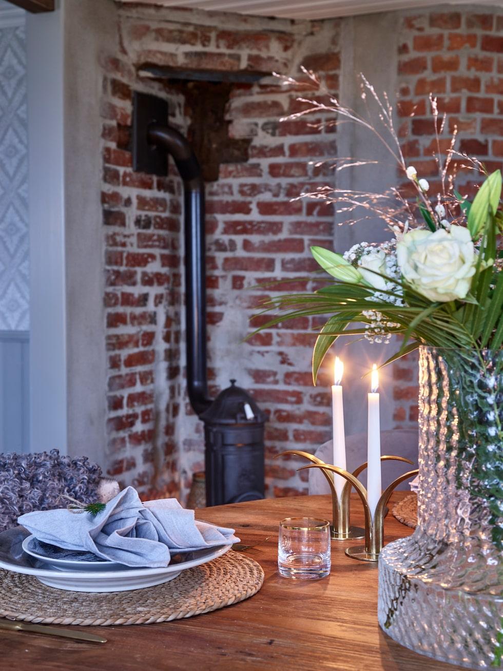 Den lilla värmande gjutjärnskaminen är tillverkad på Ebbes bruk som ligger precis nedanför berget där familjen bor. Porslin, Tyghuset Taberg. Glas, Newport. Vas, Skrufs glasbruk.