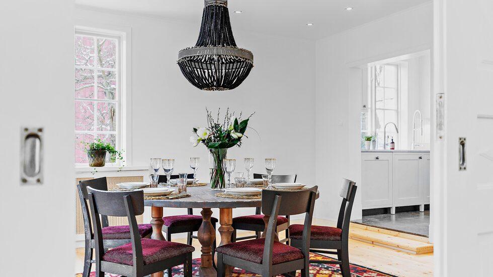 Vardagsrum och matsal ligger i fil med vackra salsdörrar och öppen spis.