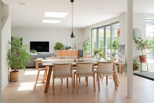 Annika är väldigt nöjd med valet av plankgolv av Douglasgran, som paret har i köket och vardagsrummet. Det blir ett varmt och vackert inslag att se på samtidigt som det är mjukt och skönt att gå på. Bord och stolar, Kostallet Design. Taklampa Semi Pendel, Gubi. Svart ljusstake, Kubus.
