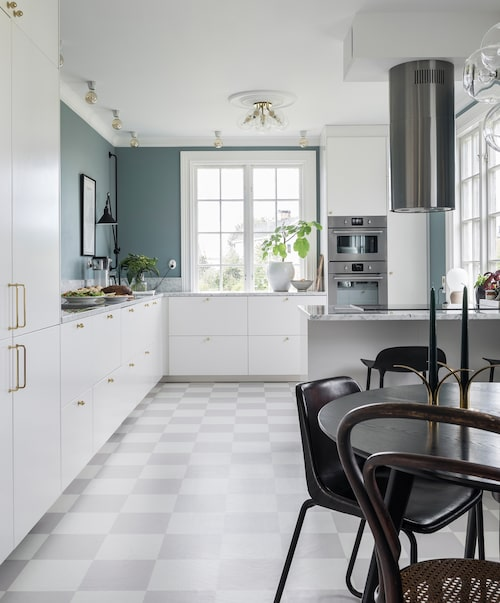 Influencern Mimmie Lidmår har skapat ett kök som sticker ut. De stilrena, vita skåpluckorna är från Ikea och den blågrå väggen är målad i kulören blåstång från Alcro.