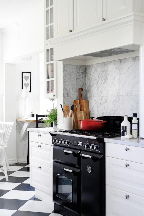 Den svarta gasspisen från Falcon bryter av snyggt till det vita köket, och fläkten göms på ett snyggt sätt i de platsbyggda skåpen. Marmorplattor på väggen agerar stänkskydd och blir ett vackert blickfång. Skärbrädor, Jamie Oliver.