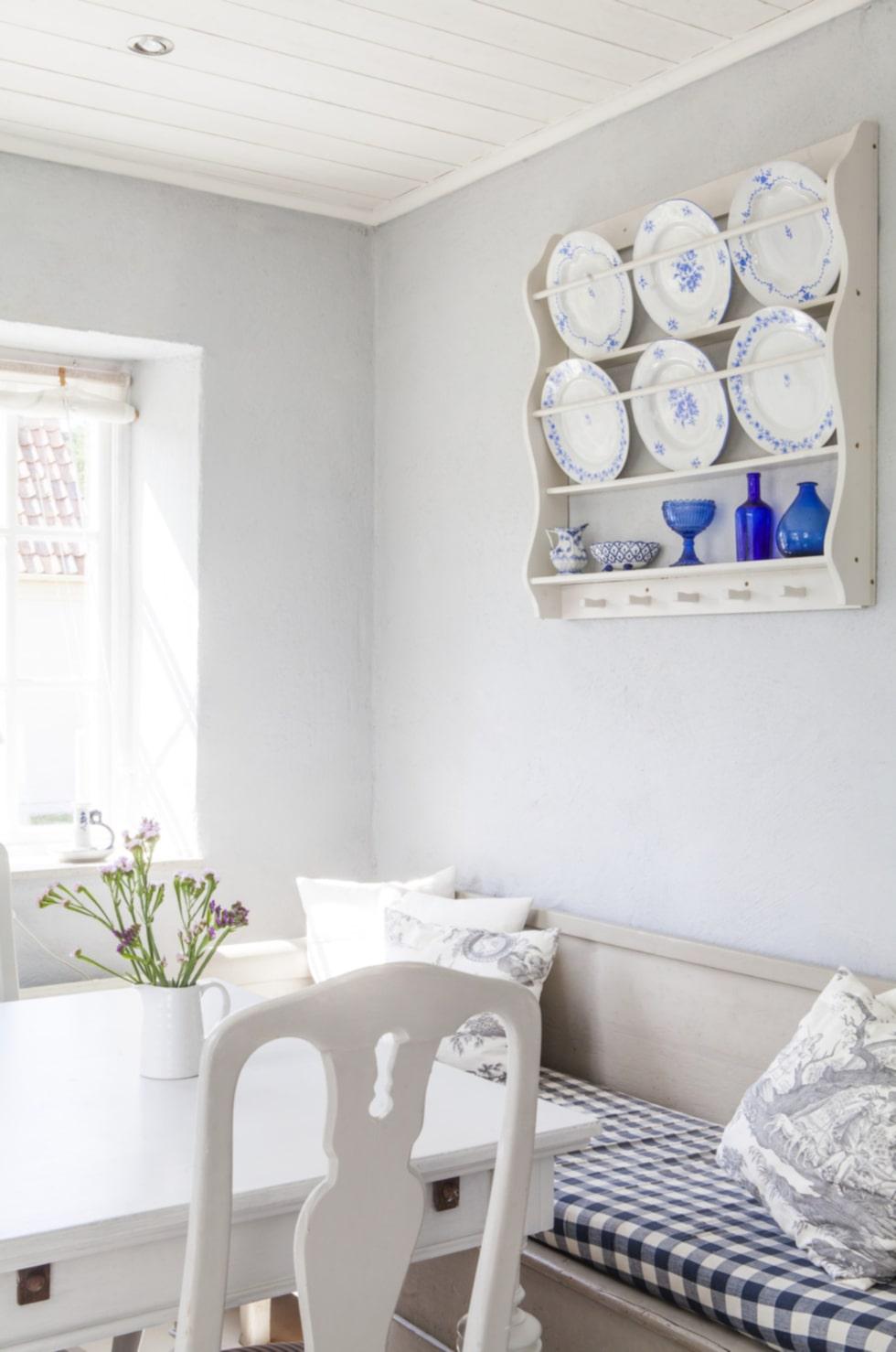 Gammalt porslin i vitt och Matsalsdelen i köket går i gammal stil – stolen kommer från Ikeas 1700-talsserie som inte längre tillverkas. Soffan är klädd med blå-vitt tyg i så kallad Gripsholmsruta.