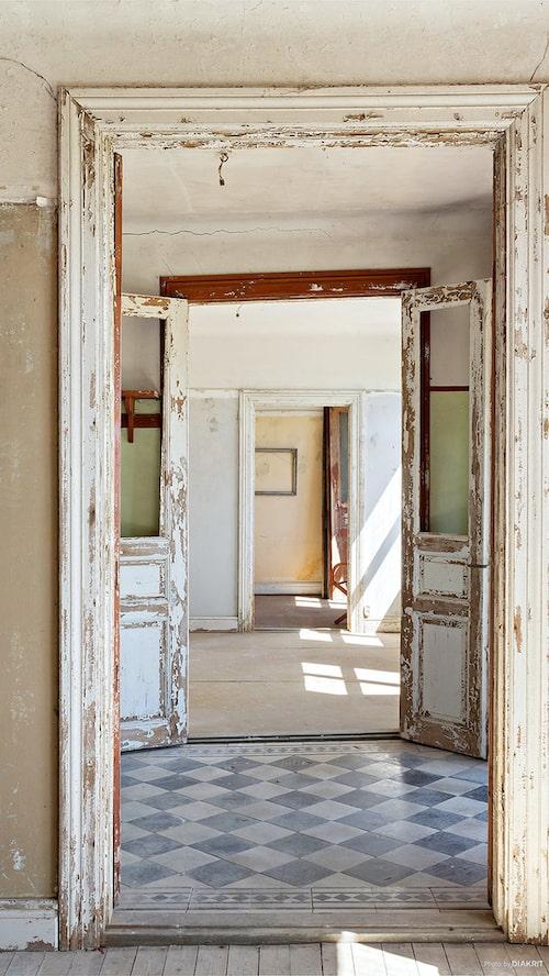 Entré till hallen, keramiken på golvet är schackrutigt stengods med meanderbård. Snygga spegeldörrar i par.