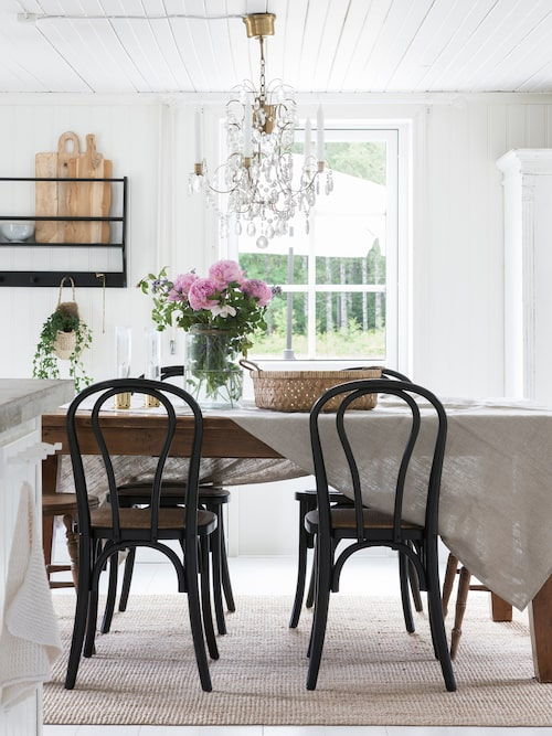 Kristallkronan ovanför köksbordet sprider ett vackert sken. Camilla har plockat in en härlig bukett med pioner från trädgården. Stolar, Ellos. Kristallkrona, Markslöjd.