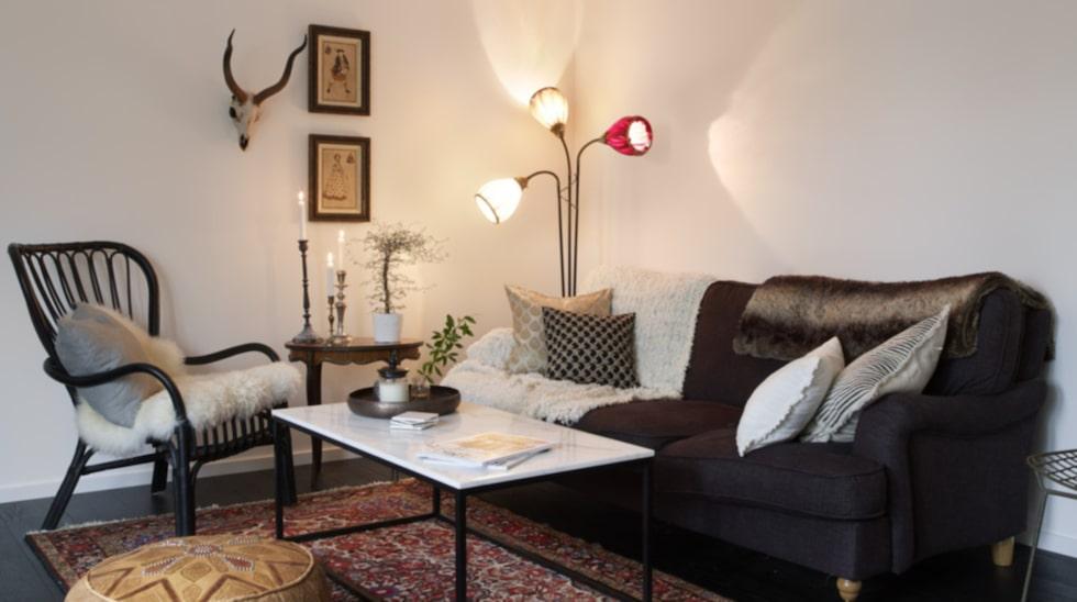 """Favoritlampa. """"Den trearmade golvlampan är en av de saker jag älskar mest i mitt hem. Som tur är har jag en mamma som är skräddare och hon kunde sy nya lampskärmar i de färger jag önskade"""", säger Lovisa. Mattan är en äkta persisk matta och ett auktionsfynd. Soffan är även den ett fynd från Facebook. Bord från Furniturebox."""