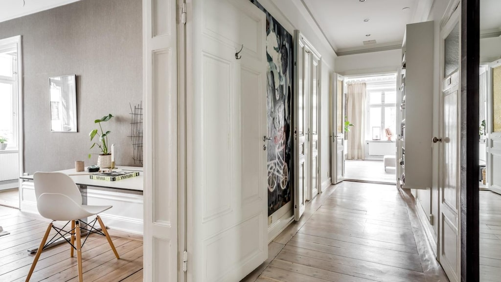 Lång, ljus och med vacker belysning tar hallen oss till lägenhetens alla rum. Brädgolv i original, vitmålade väggar och avhängningsmöjligheter. Säkerhetsdörr till trapphuset. Fin stuckatur och ljusarmaturer med dimmer.
