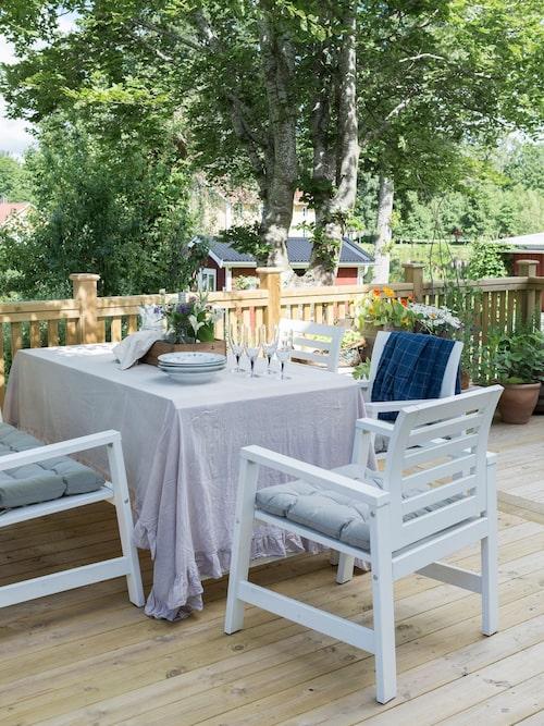 På den rymliga altanen äts de flesta måltiderna under sommaren. Utemöbler och dynor, Ikea.