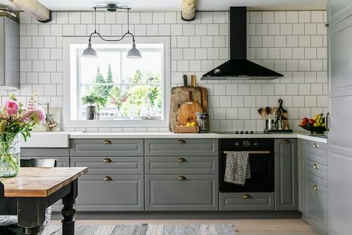 Det stora lantliga köket har synliga takbjälkar, stramt kakel, marmorbänk och gammaldags profilluckor i grått. Fönstret är placerat så att man har utsikt från arbetsbänken. Kök, Bodbyn, och dubbel porslinsho, Ikea.  Blandare, Camargue Retro, Bauhaus.