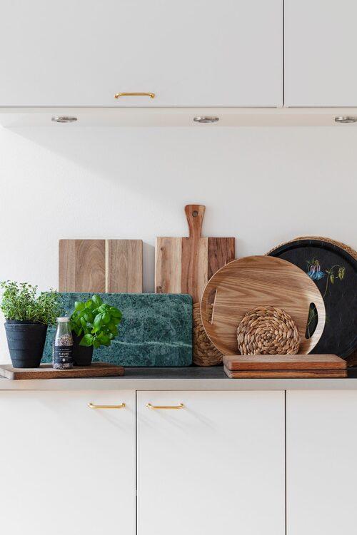 Nya handtag i mässing, nylackerade skåpsluckor, dekorativa skärbrädor och kryddväxter ger köket ett estetiskt lyft.