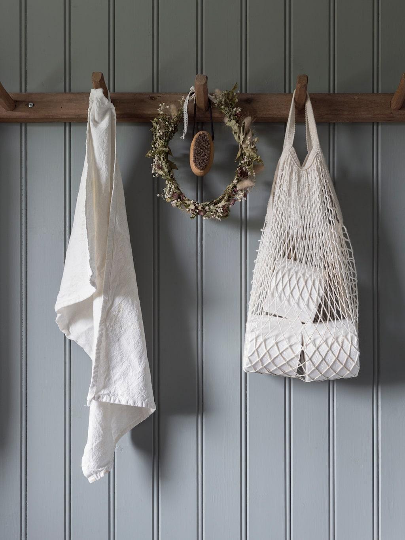 På badrummets knoppbräda hänger minnen från sommaren, som den torkade blomsterkransen som Elin bar på midsommarafton. Toarullarna förvaras i en nätkasse. Kasse, Ikea.