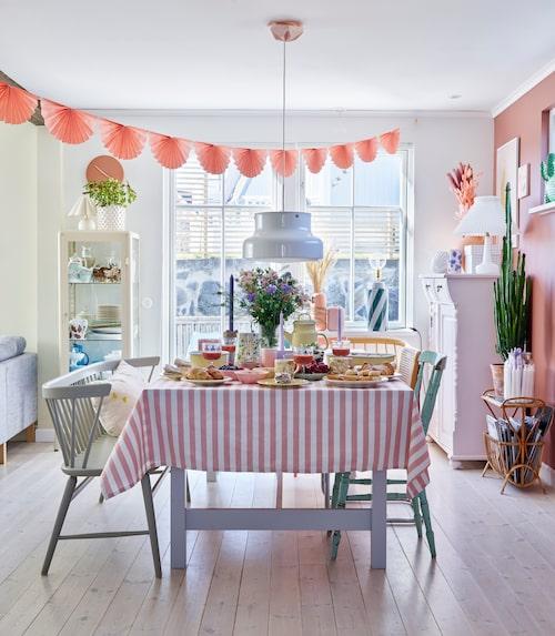 Matbordet är uppdukat till fika med hembakade hallongrottor, mandelmusslor och bananbröd med färska bär och grädde. Bumlinglampan är ett fynd som Julias mamma räddade från en container. Vimpel, Lagerhaus. Duken är hemmasydd. Emaljkanna, form och skål, Kockums. Glasen är arvegods. Gult och rosa porslin, Hay. Den rosamålade skänken har Viktors pappa byggt. Köksbord, köksstolar och de båda pinnsofforna är second hand-fynd.