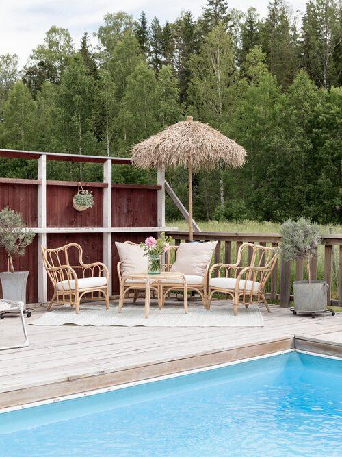 För att skapa lä och ett varmare klimat vid poolen har paret ramat in den med ett plank som de målat in i samma kulör som huset och byggnaderna på gården. Trädgårdsmöbler, Ikea. Parasoll, Ellos.