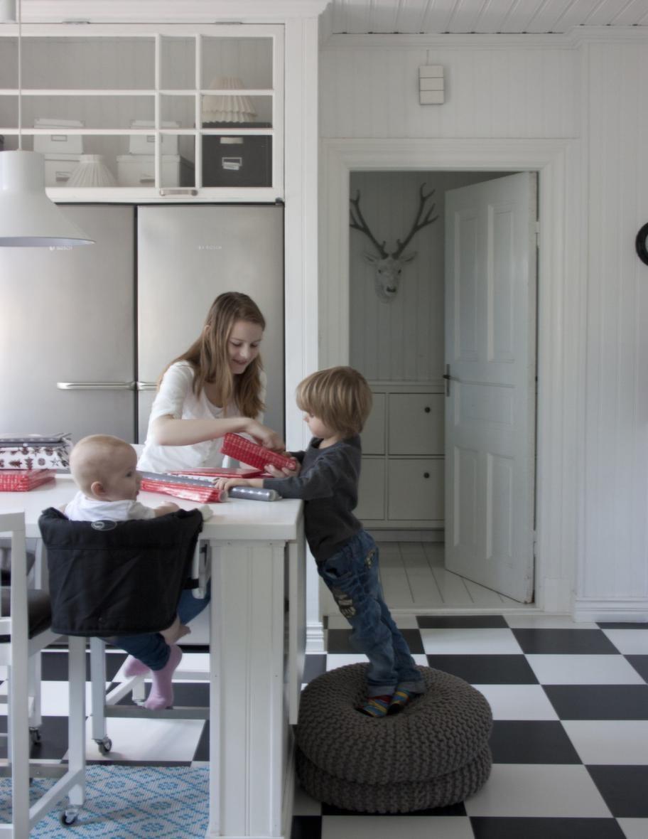 """JULPYSSEL. Barnen slår in julklappar i köket. """"Här ser man det stora fönster som vi hängt upp som vitrinlucka över kyl och frys."""""""