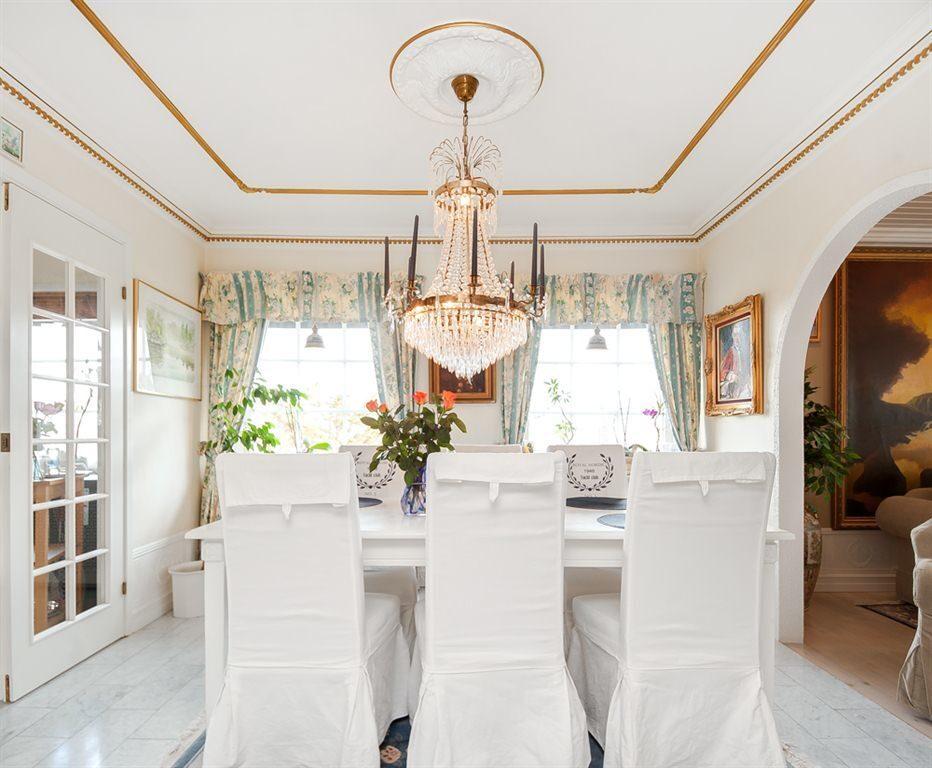 Luftig matsal med vacker takstuckatur och Carrara marmorgolv, ligger i öppen planlösning med vardagsrummet.