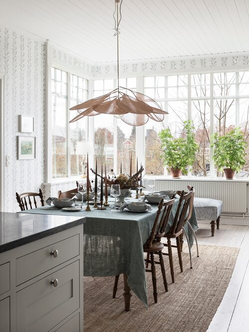 Genom att öppna upp mellan det gamla köket och vardagsrummet har familjen fått ett stort och luftigt kök med en matplats som rymmer många. Väggarna i köket är tapetserade med tapeten Pil från Sandberg Wallpaper.