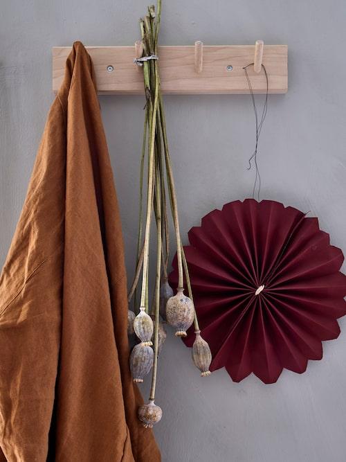 På knoppbrädan hänger en morgonrock i rosttoner tillsammans med torkade fröställningar och en pappersblomma. Morgonrock, H&M.