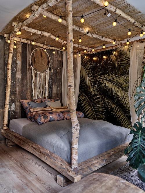 Sängen är byggd av björkstammar och har ett tak av bambu. Väggen bakom sängen är byggd av återvunna brädor.
