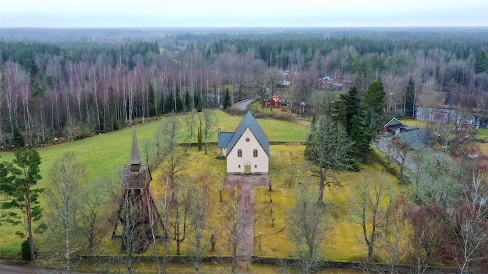 På marken intill kyrkobyggnaden finns en klockstapel i trä.