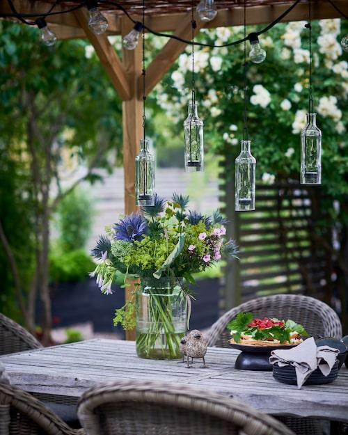 Hänglyktorna med plats för värmeljus glittrar vackert i solen om dagarna och ger mysbelysning på kvällarna. Buketten består bland annat av tistlar och funkiablad. Glasvas, Granit. Linneservetter, Himla. Keramikfåglar från Zetas Trädgård.