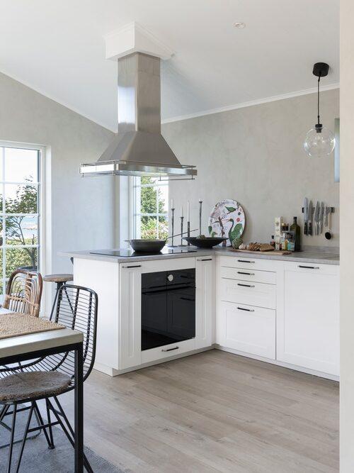 Köksinredningen är öppen mot matrummet vilket frigör mycket yta och gör att rummet känns större. Skåp, fläkt och bänkskiva, Ikea. Lampor ovanför bänken, Bistro, Hallbergs belysning.