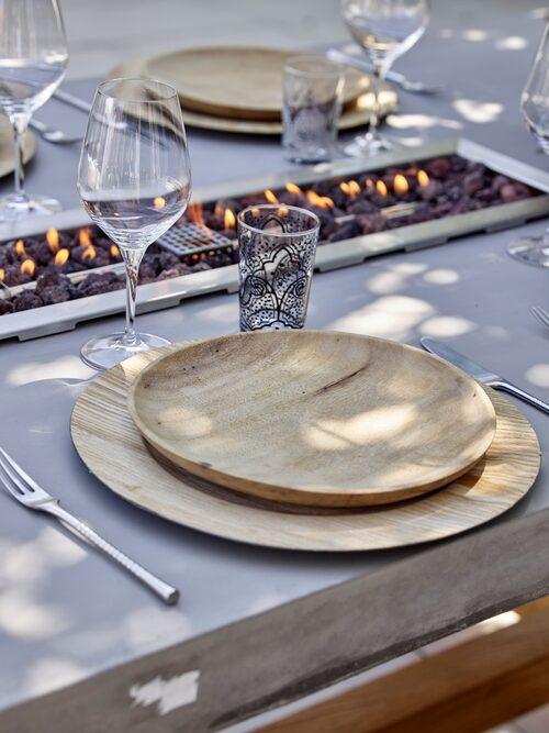 Det snygga betonbordet har en kanal i mitten där man kan tända en eld. Elden går på gasol. Bord, Elementi. Trätallrikar, Muubs. Glas med mönster, Majas Cottage.