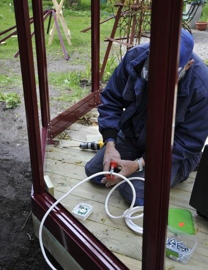 ELEKTRIKERN PÅ PLATS. Det bästa är att redan från början bestämma sig för om växthuset ska ha el och vatten så att det kan förberedas i god tid.